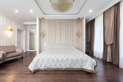 Interior of modern bedroom with bed next to armchairs under chandelier with curtains on windows