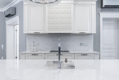 Interior of white classic kitchen with marble counter and chrome faucet in front of white cabinets next to door
