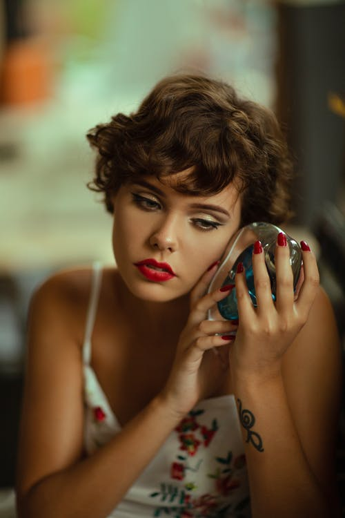 Concentrated female with makeup and short hair wearing dress listening to decorative glass conch while sitting in room on blurred background