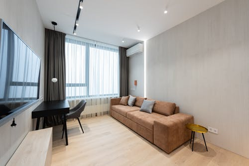 Interior of modern living room with sofa with pillows and TV on wall next to table with chair and curtains on window