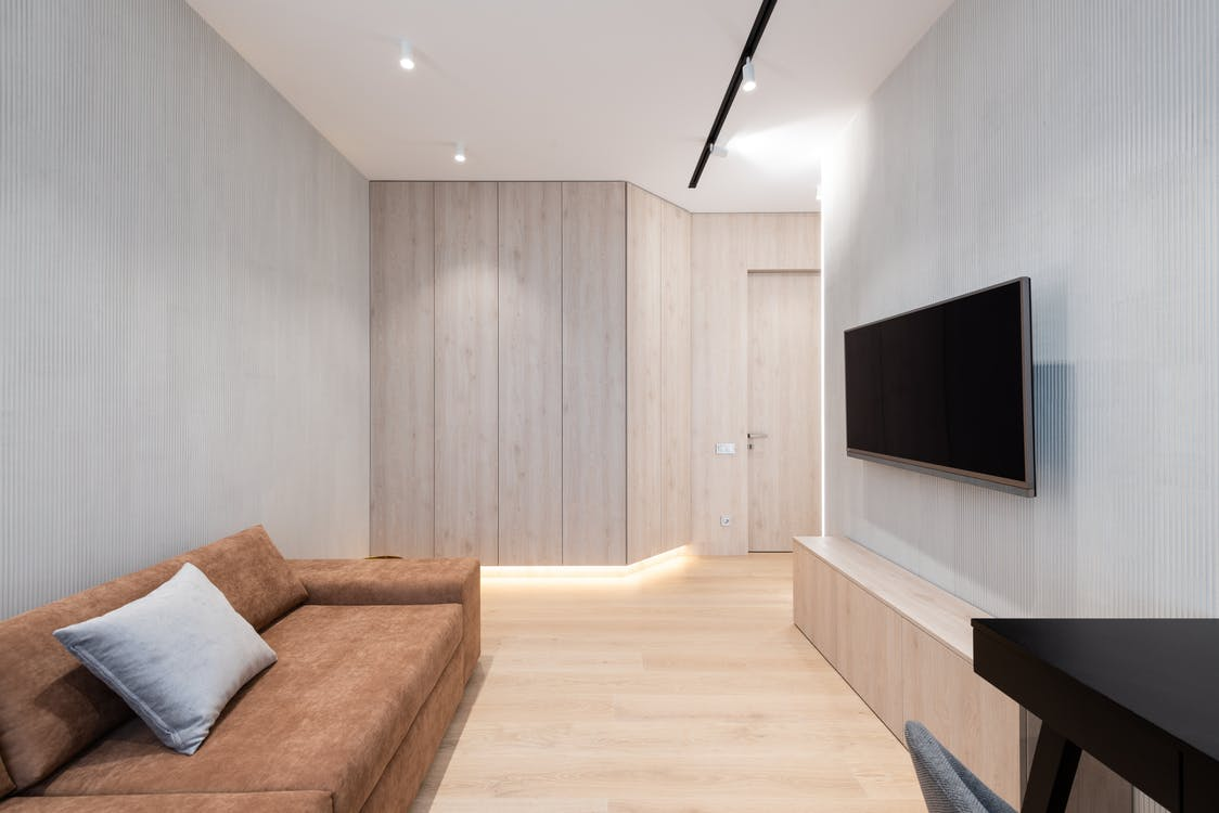 House interior with couch in front of TV on wall
