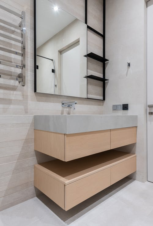 Interior of modern light restroom with sink and tap on cabinet under mirror