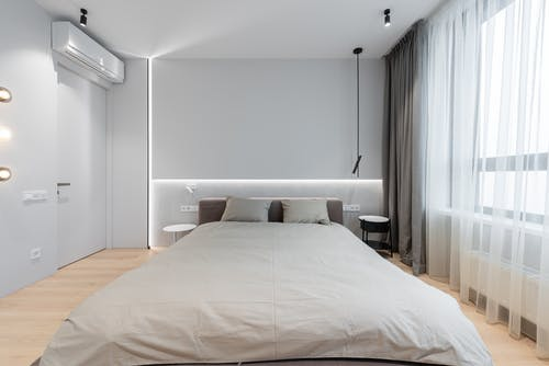 Home interior with bed next to curtains on window