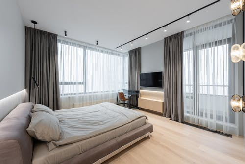 Home interior with bed next to curtains on windows