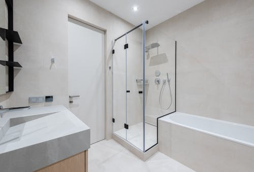 Interior of modern light bathroom with bathtub and shower next to sink with cabinet near door