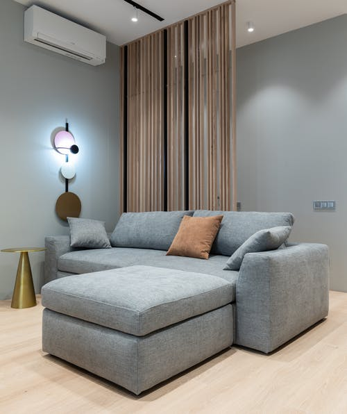 Interior of modern living room with sofa with pillows next to round table under conditioner