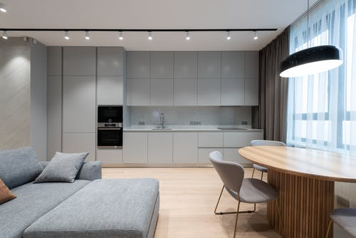 Interior of modern residential apartment with comfortable furniture and compact kitchen in grey shades