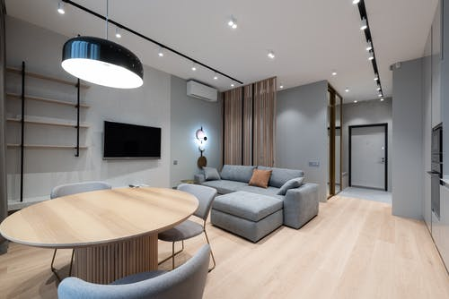 Design of comfortable studio apartment with grey walls placed near wooden table and chairs