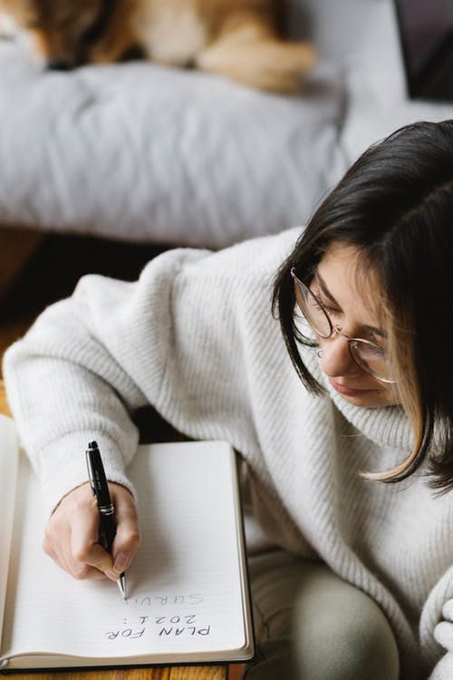 From above of crop young female in warm clothes and eyeglasses writing plan for 2021 in notebook while sitting on floor near sleeping Akita Inu dog