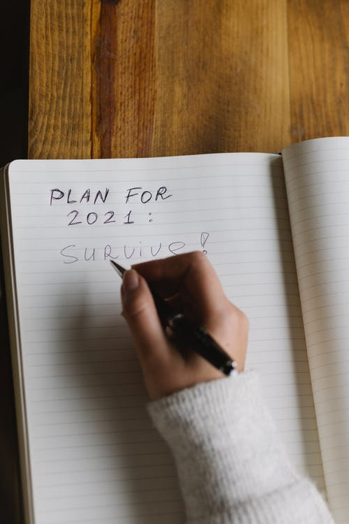 From above of crop faceless lady in warm clothes writing Plan For 2021 and Survive text in diary sitting at wooden table