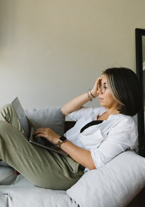 Woman in White Long Sleeve Shirt and Gray Pants Sitting on Gray Couch