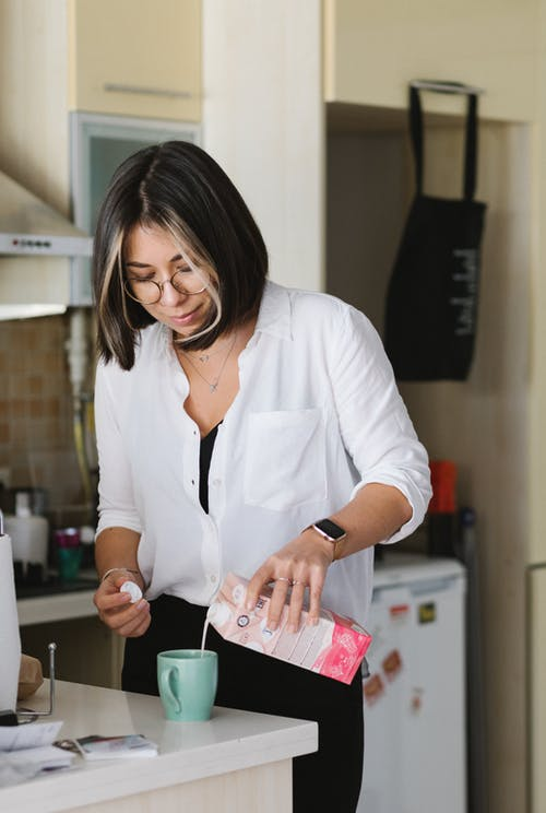Glad young female in white shirt pouring fresh milk from carton pack into ceramic cup in contemporary kitchen