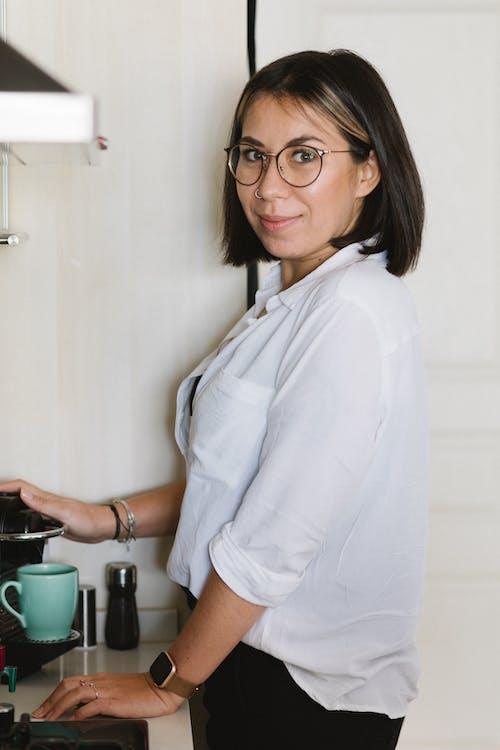 Content woman brewing coffee using pod machine