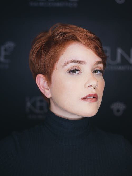 Young ginger female with stylish short haircut and piercing looking at camera on blurred background