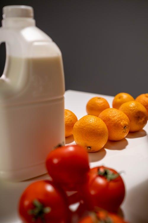 Orange Fruits Beside White Plastic Pitcher