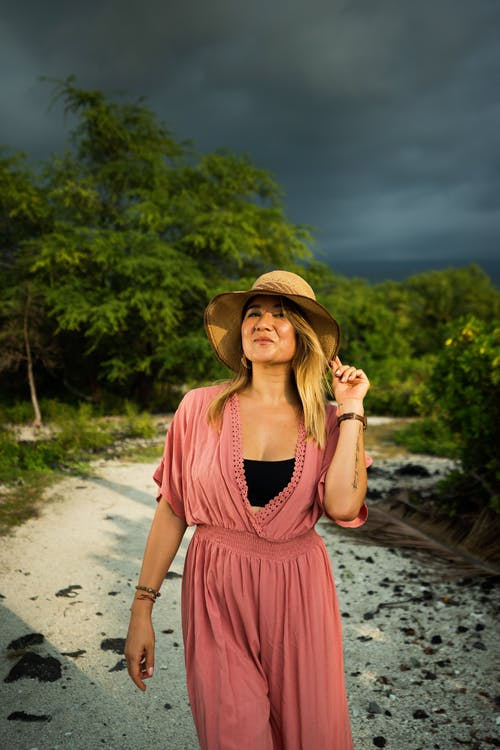 Woman in trendy dress and hat under cloudy gloomy sky