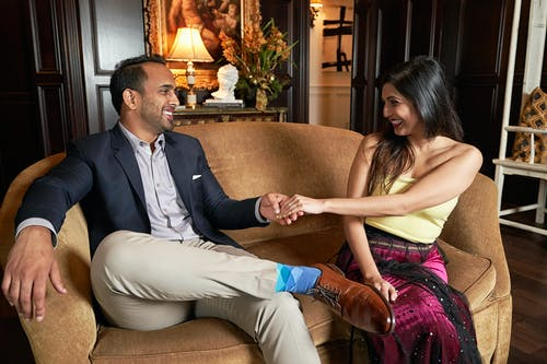 Positive ethnic woman and man in stylish outfits looking at each other and smiling in comfortable hall