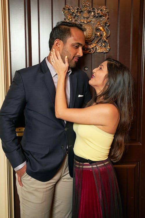 Tender ethnic couple caressing near door