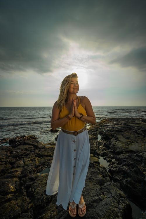 Full body of peaceful female with folded hands doing surya namaskar asana with closed eyes while standing on stony beach near sea