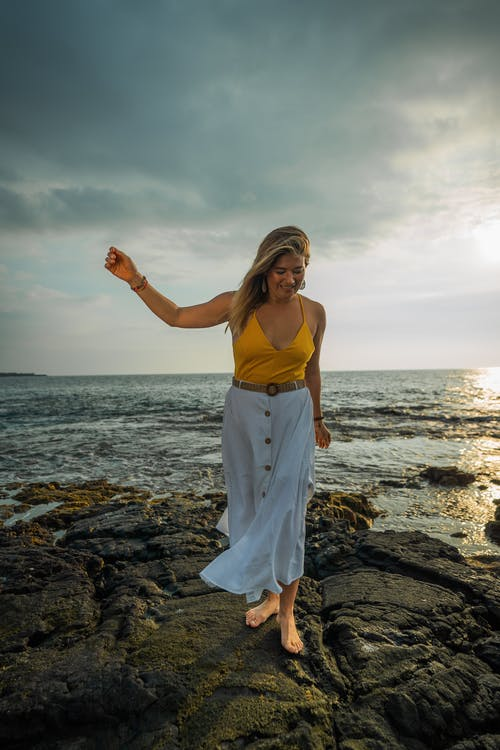 Full body of positive barefoot female traveler strolling on stony shore near rippling sea in tropical country during summer vacation