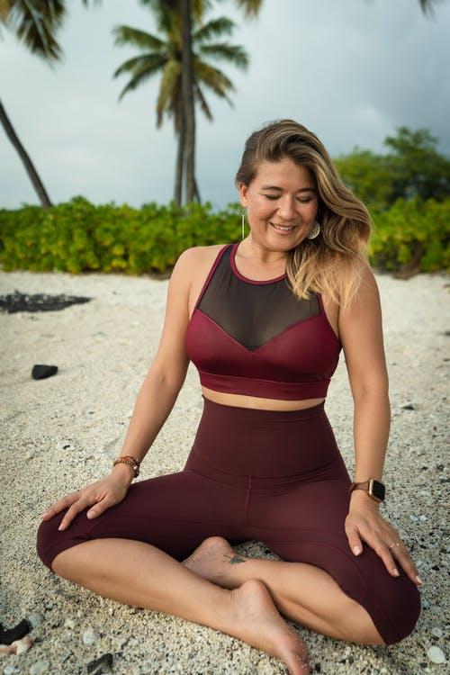 Full body of cheerful female traveler in activewear looking down while sitting with crossed legs in tropical country with exotic palms