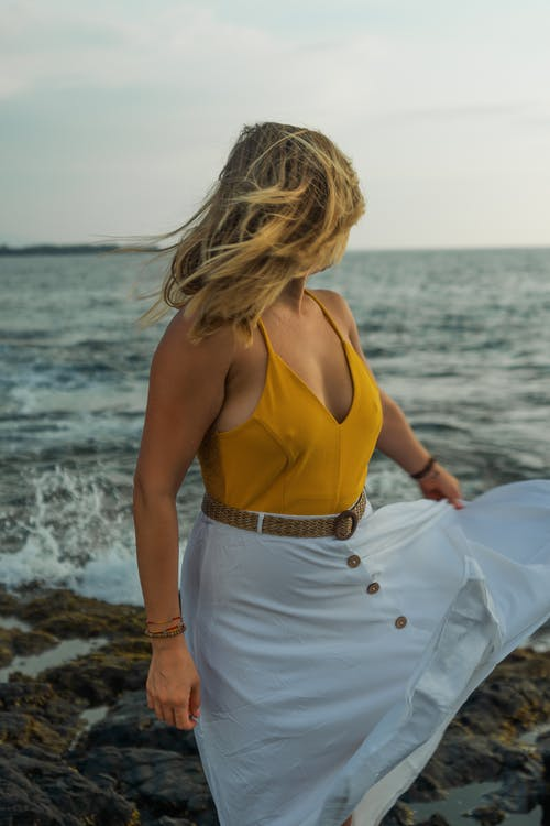Side view of unrecognizable female traveler with white skirt and yellow top standing on stony near waving sea during summer vacation in tropical country