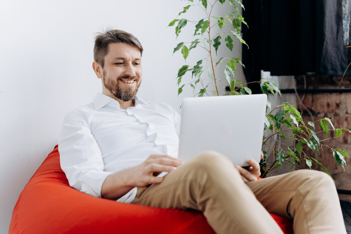 A Happy Man Using His Laptop