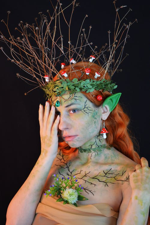 Lady wearing enchantress costume with decorative elements and body art