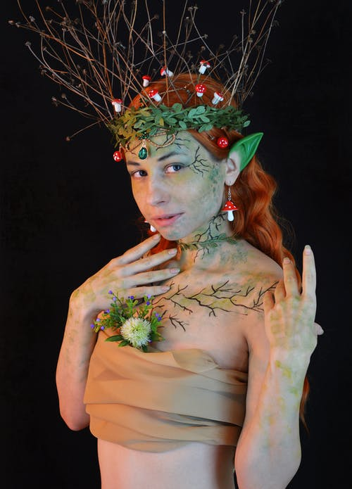Young lady wearing enchantress costume with green wreath with leaves and twigs and body art with small decorative mushrooms in hair and fake ears looking away on black background