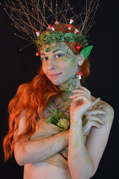Young lady wearing enchantress costume with body art and green wreath with leaves and twigs with small decorative mushrooms in hair and fake ears looking at camera on black background