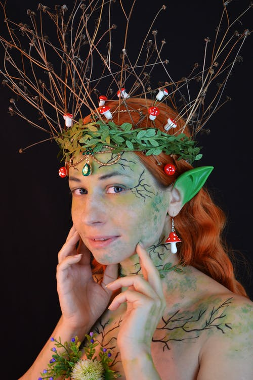 Confident lady wearing enchantress costume and body art with decorations