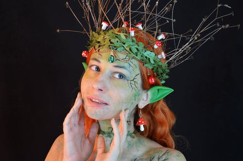 Young lady wearing enchantress costume with body art and green wreath with leaves and twigs with small decorative mushrooms in hair and fake ears looking away on black background