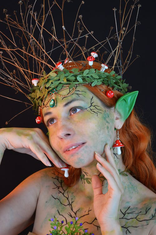 Portrait of fanciful young female with elven makeup and pointy green ears wearing circlet of plants and amanita accessories on head