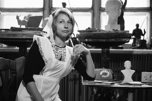 Black and white of young dreamy female in Soviet school uniform sitting on chair near table with retro telephone and books and looking away thoughtfully
