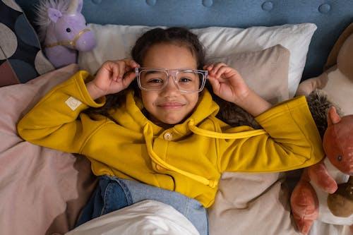 A Girl Wearing a Yellow Hoodie Lying Down