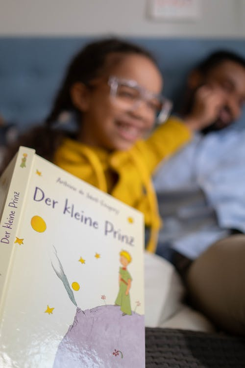 Close-Up Shot of Kid's Book with a Girl Background
