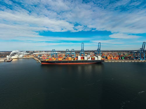 High angle of cargo ship moored in modern industrial port under blue cloudy sky in daylight