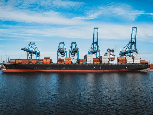 Large cargo ship with colorful metal containers floating on rippling water of ocean under cloudy blue sky in daylight