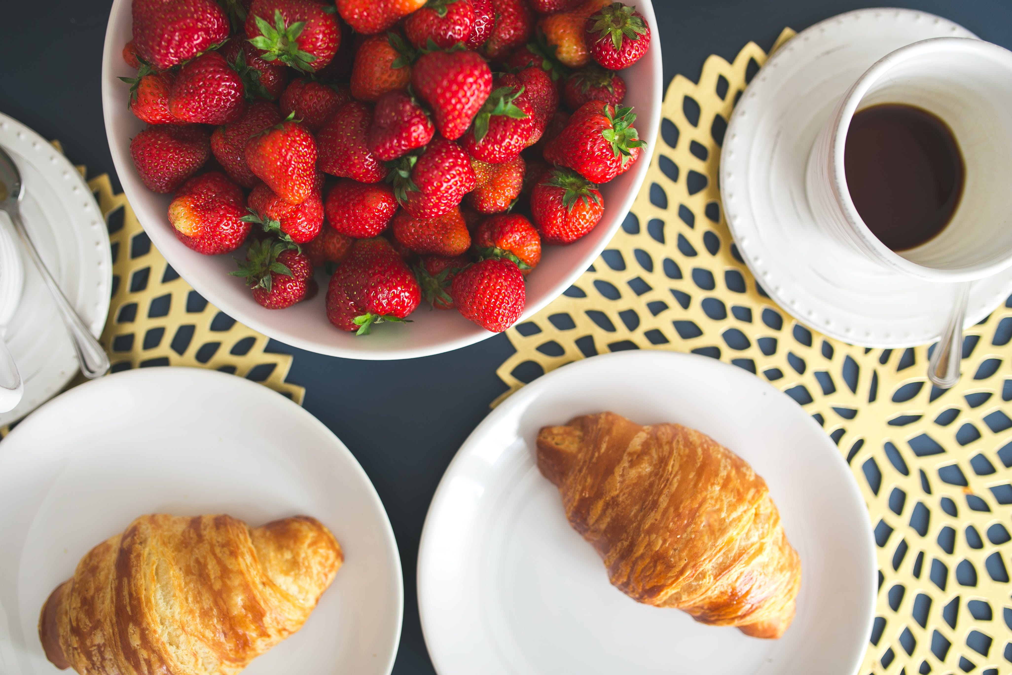 Fresh buttery croissants, hot cup of coffee and bowl with strawberries