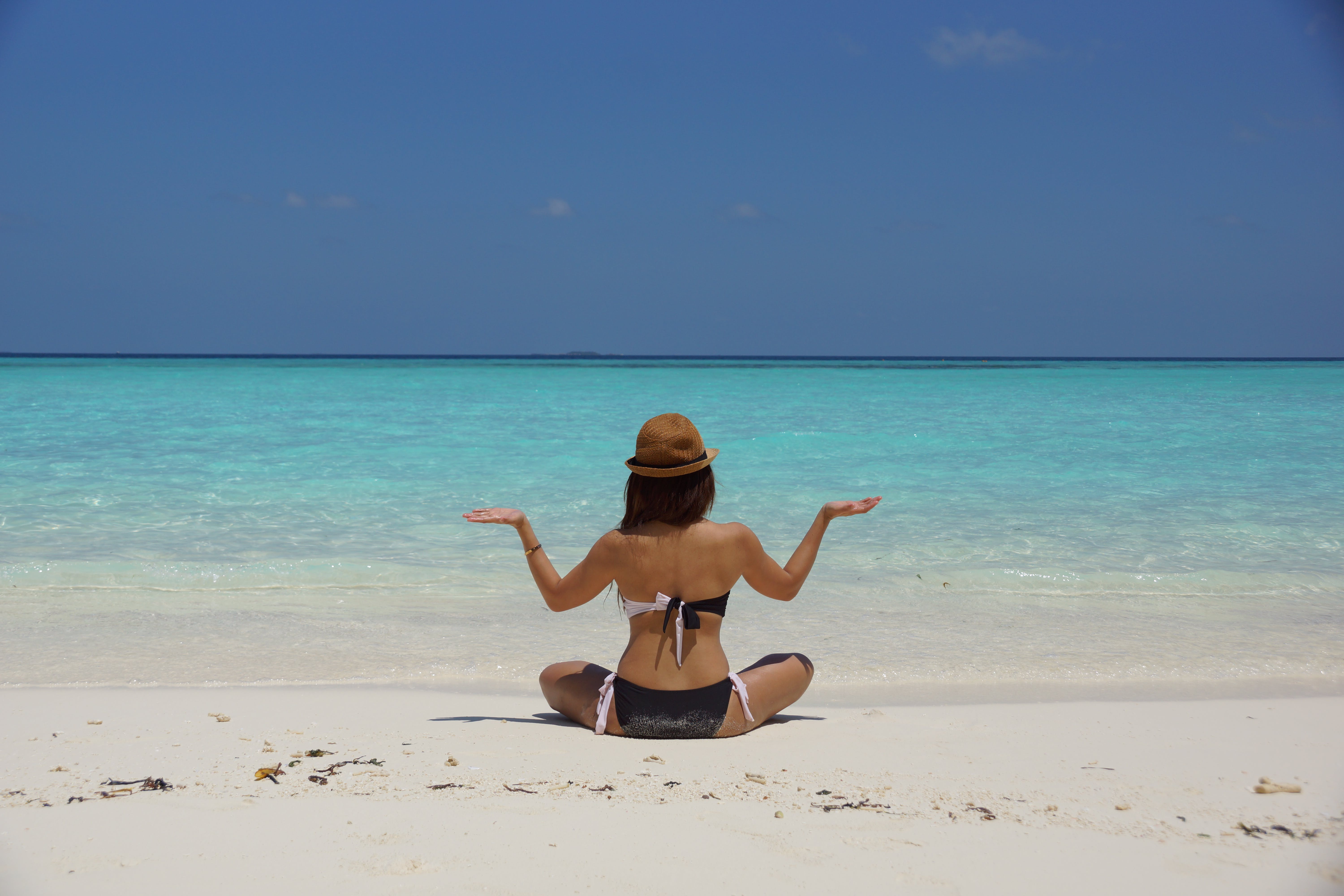 Woman in Black and White Bikini Sitting on White Stand Facing Beach during Daytime