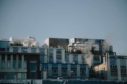 Factory building emitting smoke in industrial district