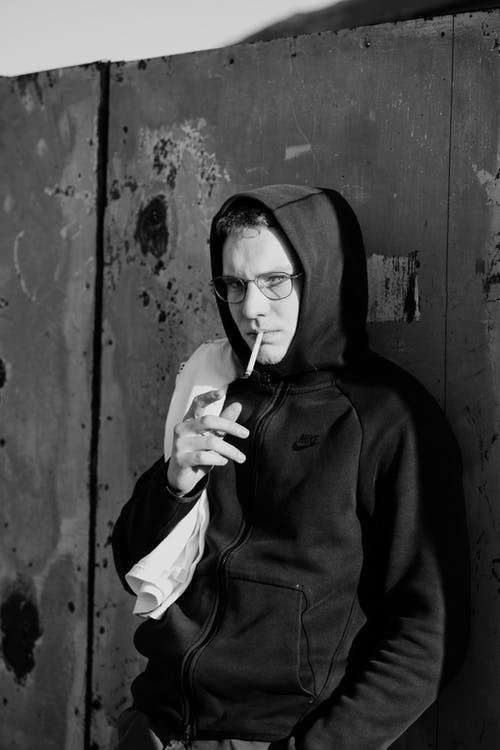 Black and white of serious young male millennial in hoodie and eyeglasses smoking cigarette and at camera while leaning on shabby wall on street