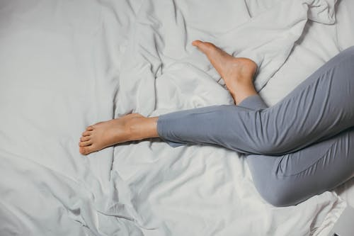 From above of crop unrecognizable barefooted female in pajama relaxing on comfortable bed at home