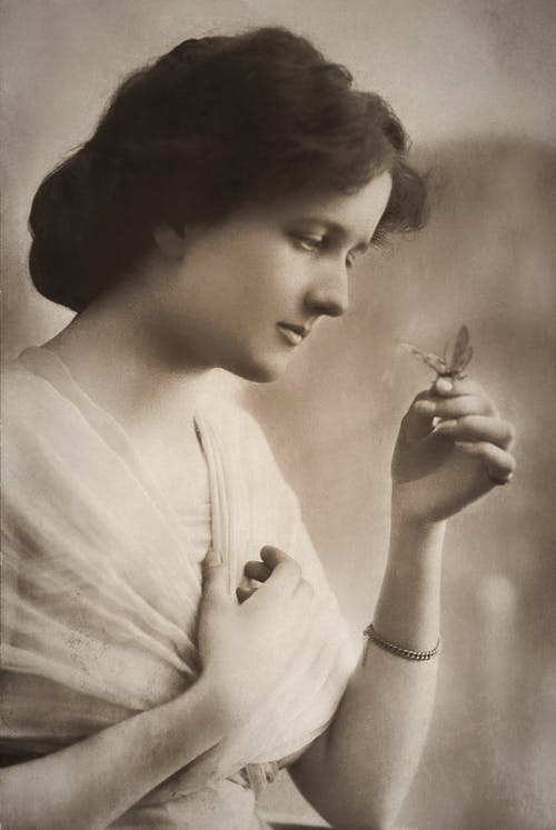 Woman With Sad Face Looking At A Butterfly On Her Hand