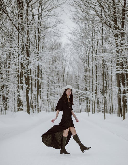 Side view of young fashionable Asian lady in black dress and whiter hat walking on snowy pat between bare trees on winter day