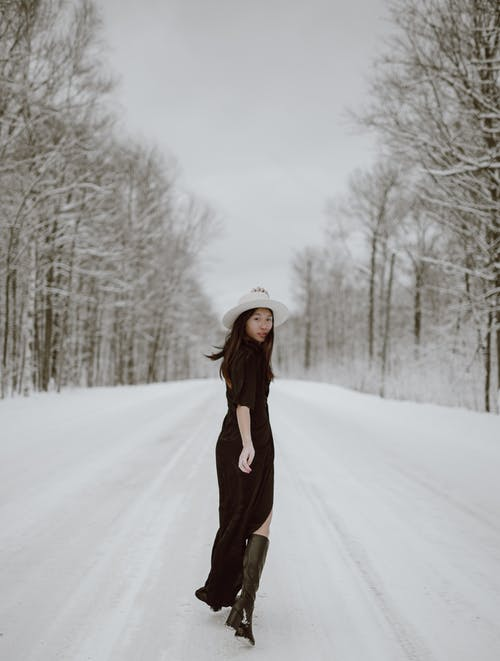 Trendy young Asian female model walking in forest on winter day
