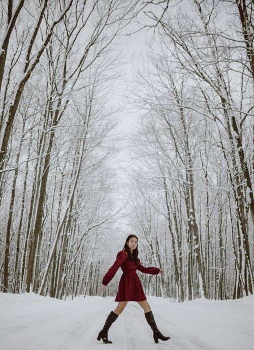 Side view full length of young gorgeous Asian female in red dress and boots walking on path covered with snow in woods with tall bare trees