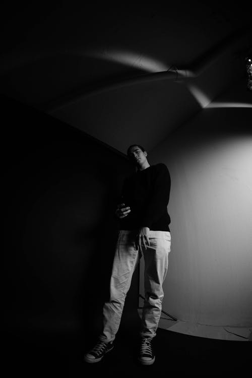 Black and white of young full body male in contemporary spacious photo studio