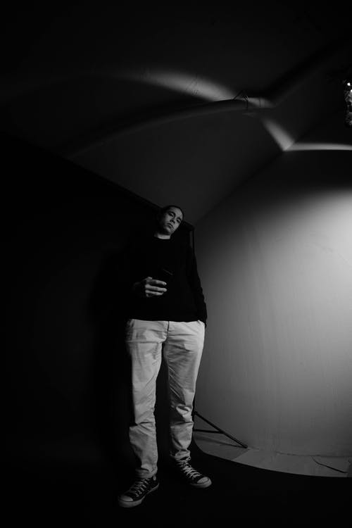 Cool man with smartphone in photo studio