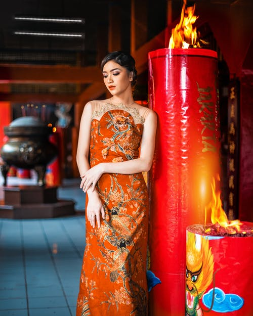 Stylish ethnic woman standing near burning fire in shrine